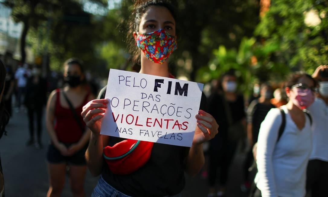 """Uma manifestante mostra um cartaz com a inscrição """"Pelo o fim de operações violentas nas favelas"""" enquanto participa do protesto em Laranjeiras Foto: PILAR OLIVARES / REUTERS"""