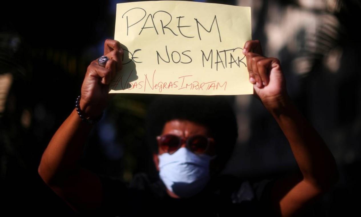 """Um manifestante mostra cartaz com a inscrição """"Parem de nos matar"""" antes do confronto com policiais Foto: PILAR OLIVARES / REUTERS"""