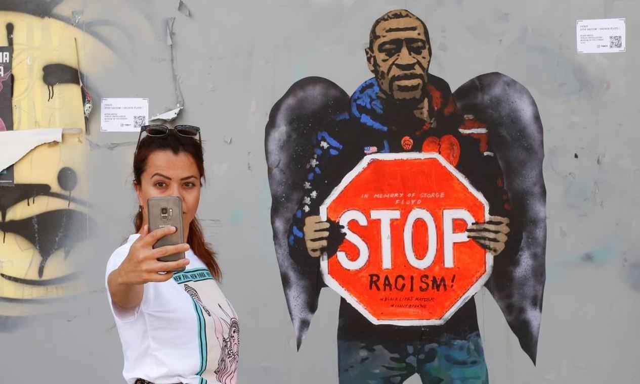 Uma mulher faz uma selfie ao lado de um grafite representando George Floyd com asas de anjo e segurando uma placa de trânsito contra o racismo, em Barcelona Foto: PAU BARRENA / AFP