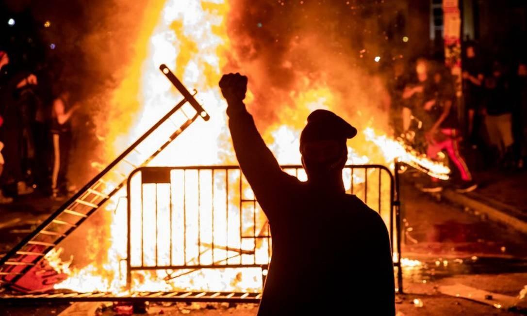 Manifestante ergue o punho, gesto símbolo do movimento negro, durante protesto no lado de fora da Casa Branca Foto: SAMUEL CORUM / AFP