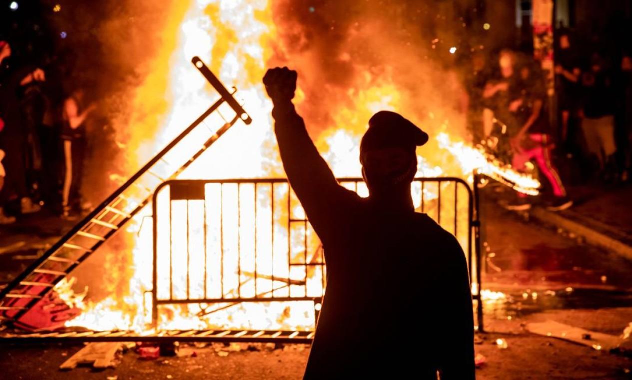 Manifestante ergue punho cerrado, gesto eternizado pelos Panteras Negras, diante de fogueira feita em frente à Casa Branca, Washington Foto: SAMUEL CORUM / AFP