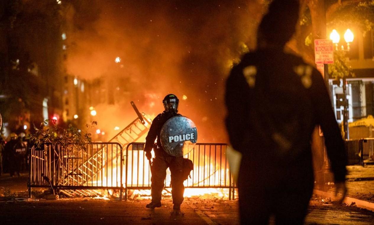 Diante da fogueira, policial encara manifestante durante protesto em frente à Casa Branca Foto: SAMUEL CORUM / AFP