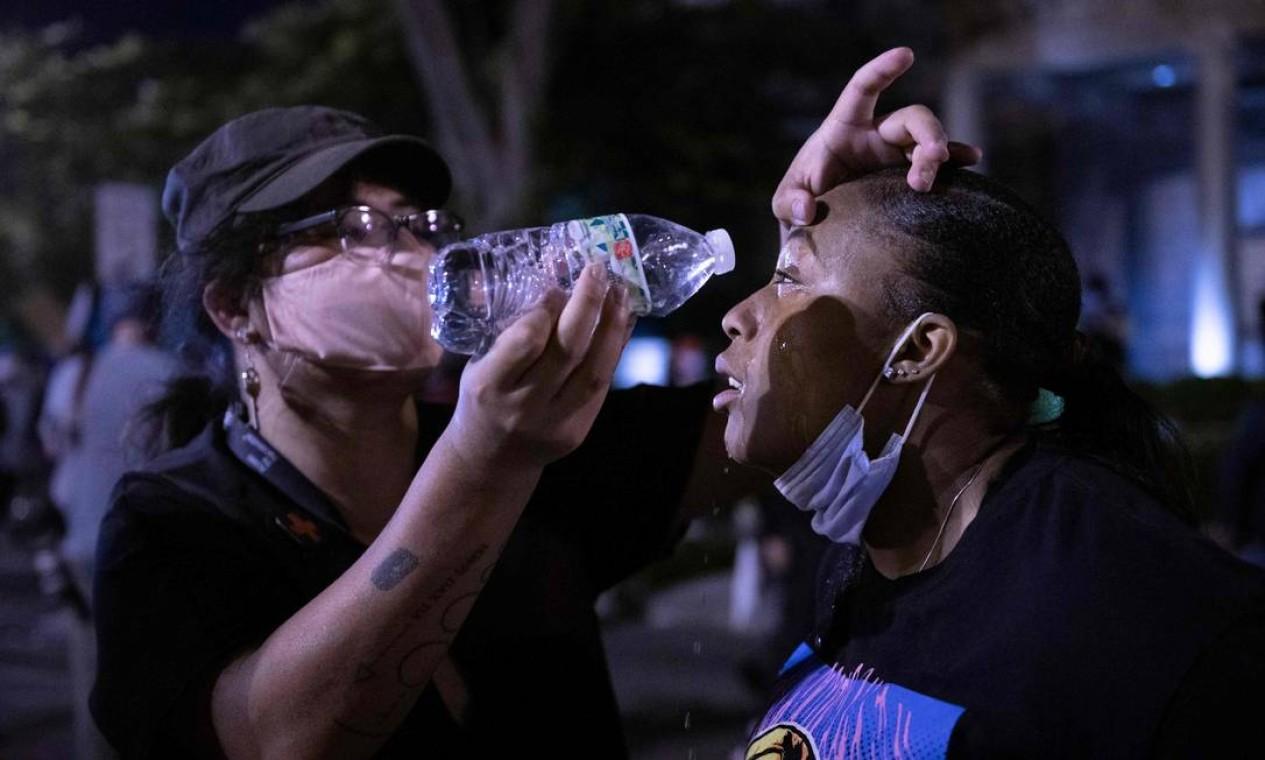 Homem limpa o rosto de companheira depois que a polícia atirou gás lacrimogêneo contra manifestantes Foto: ROBERTO SCHMIDT / AFP