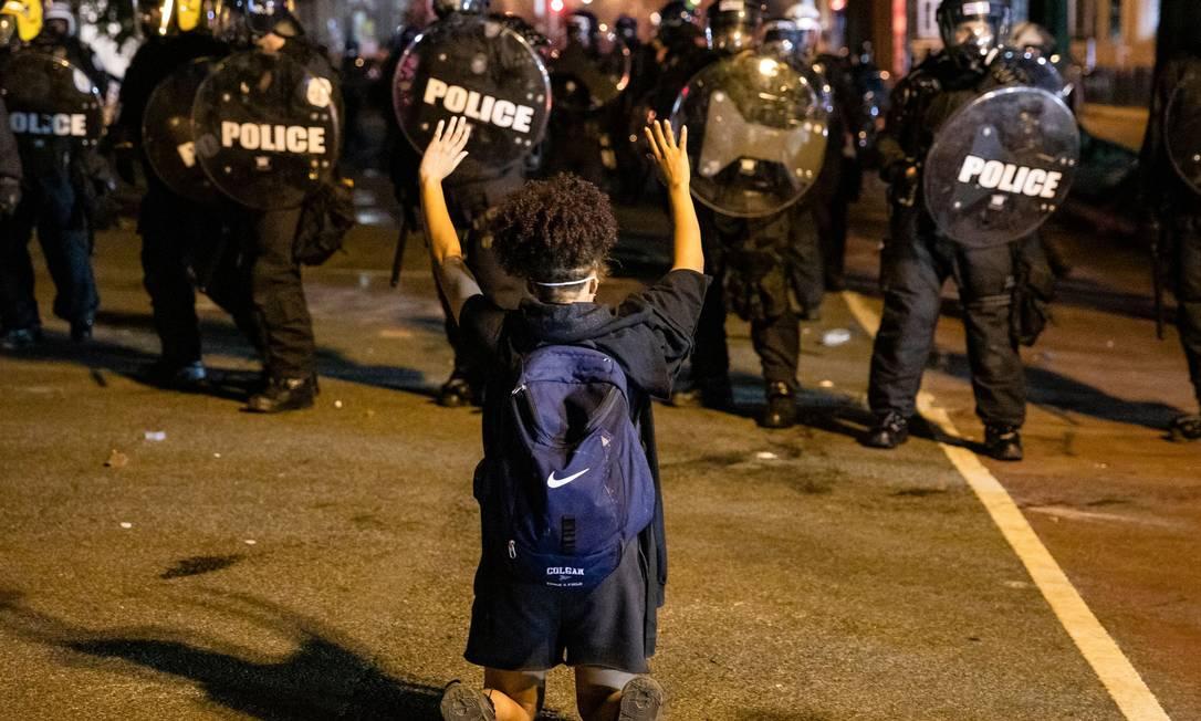 Manifestante ajoelhado mostra as mãos aos policiais da tropa de choque, durante protesto em Washington Foto: SAMUEL CORUM / AFP