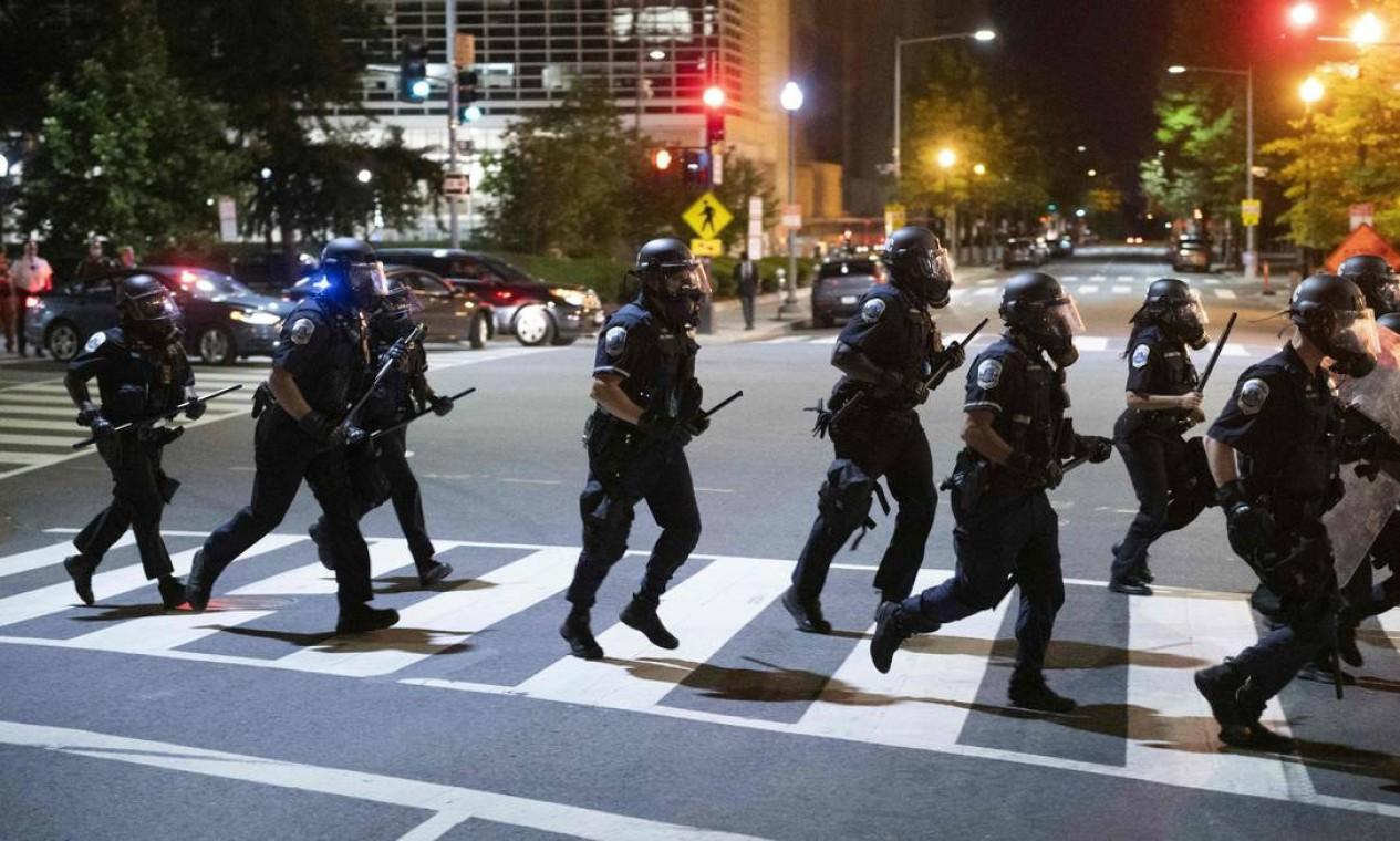Tropa corre pela faixa de pedestres em rua de Washington, para conter distúrbios, na noite de domingo Foto: ROBERTO SCHMIDT / AFP