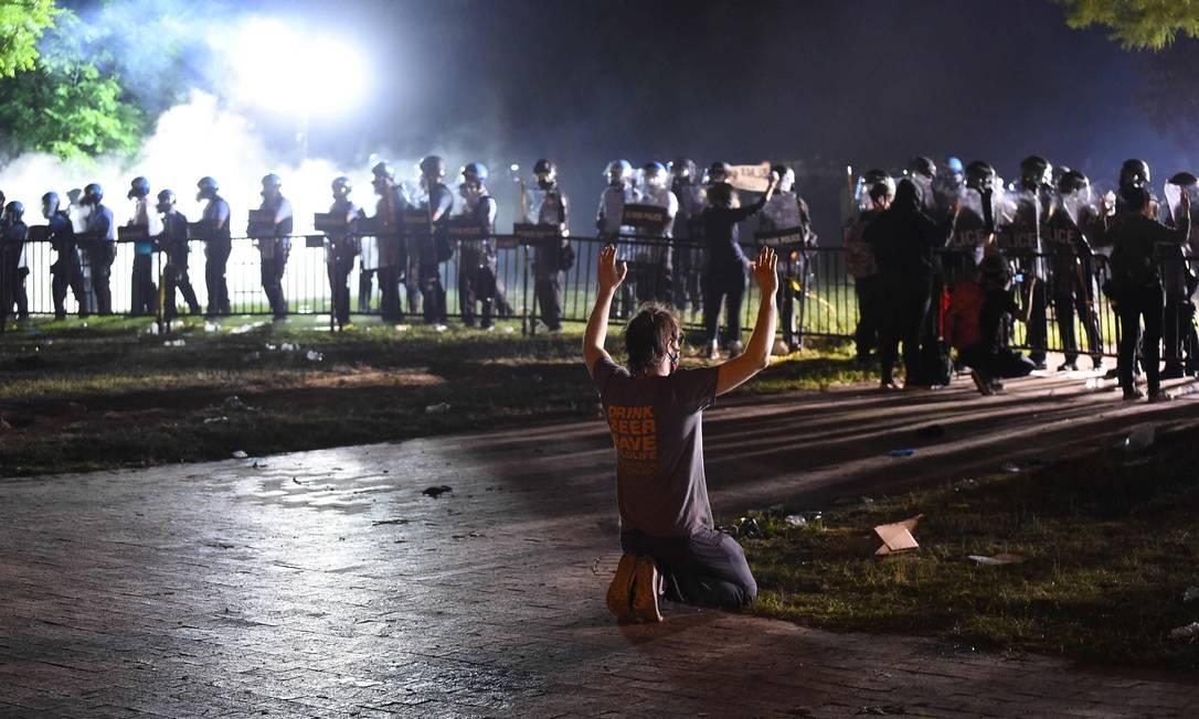 """Manifestante, de joelhos e cercado por policiais, mostra as """"mãos limpas"""" Foto: ROBERTO SCHMIDT / AFP"""