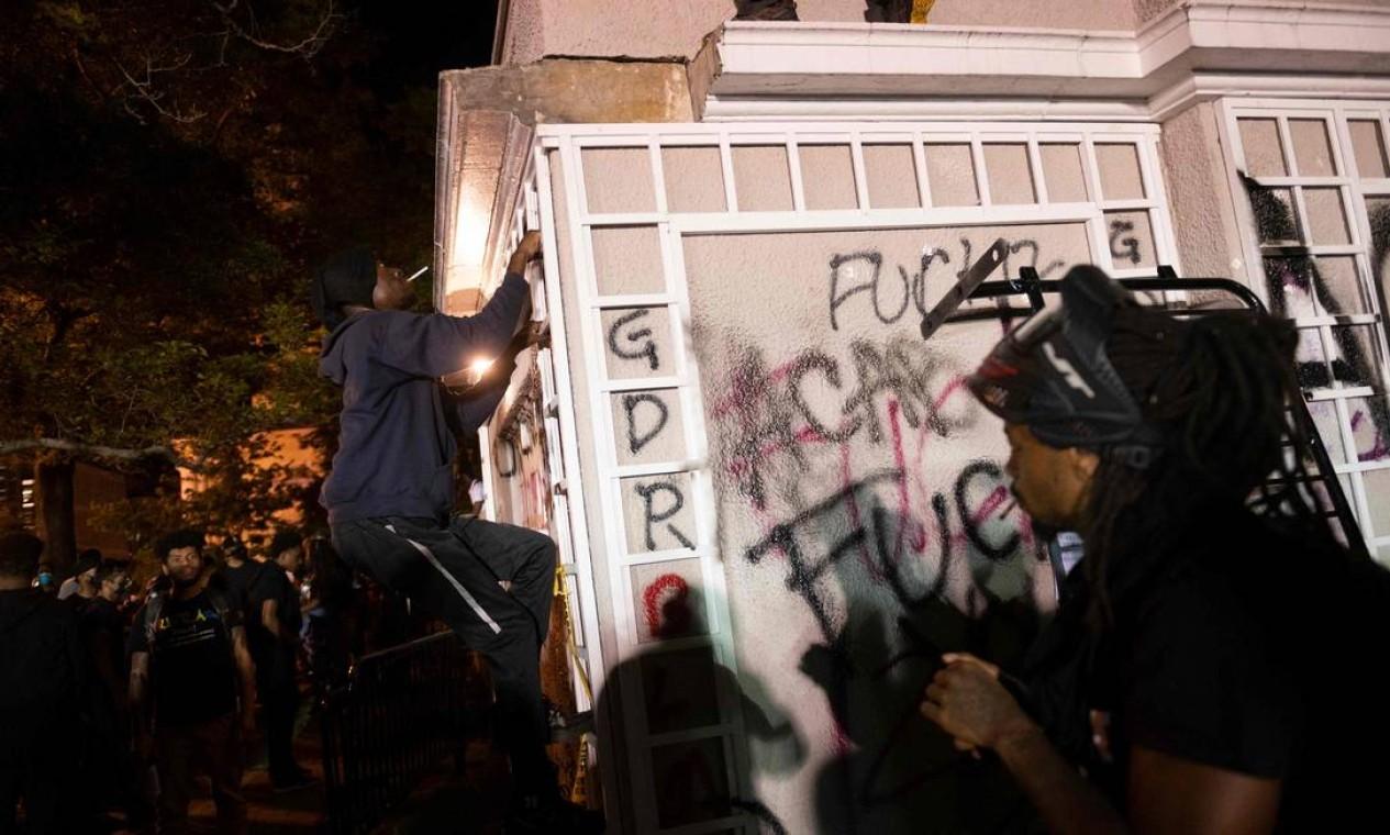 Pessoas escalam uma estrutura para incendiá-la em manifestação perto da Casa Branca, em Washington, contra o assassinato de George Floy Foto: ROBERTO SCHMIDT / AFP