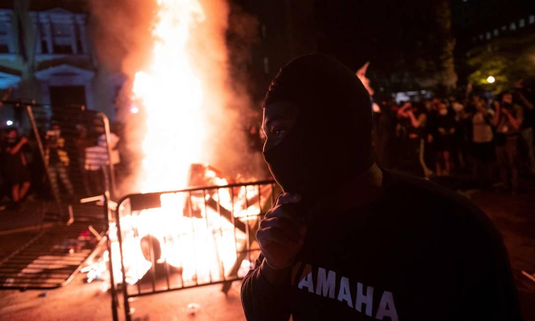 Manifestante mascarado aparece diante de fogueira feita em protesto próximo a Casa Branca, na noite de domingo Foto: ROBERTO SCHMIDT / AFP