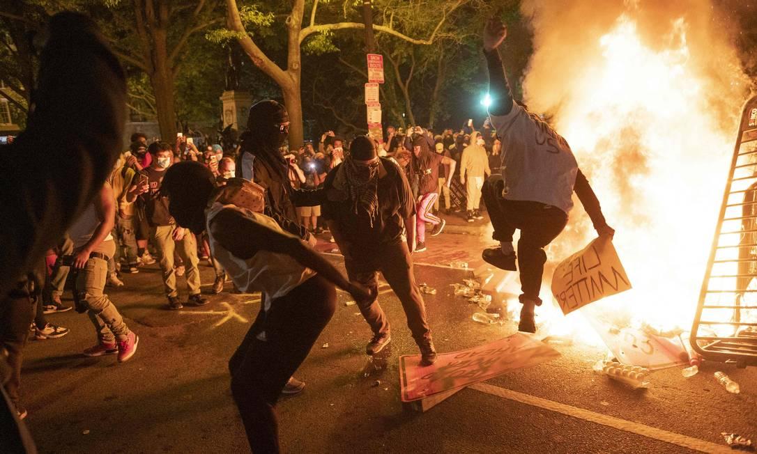 Manifestantes se reúnem perto de fogueira feita próximo a Casa Branca, em Washington Foto: ROBERTO SCHMIDT / AFP