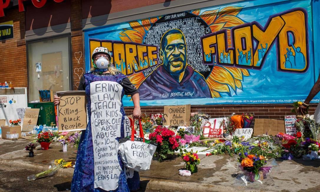 Manifestante protesta em frente à memorial para George Floyd, onde há um mural em sua homenagem na parede Foto: KEREM YUCEL / AFP / 30-5-2020