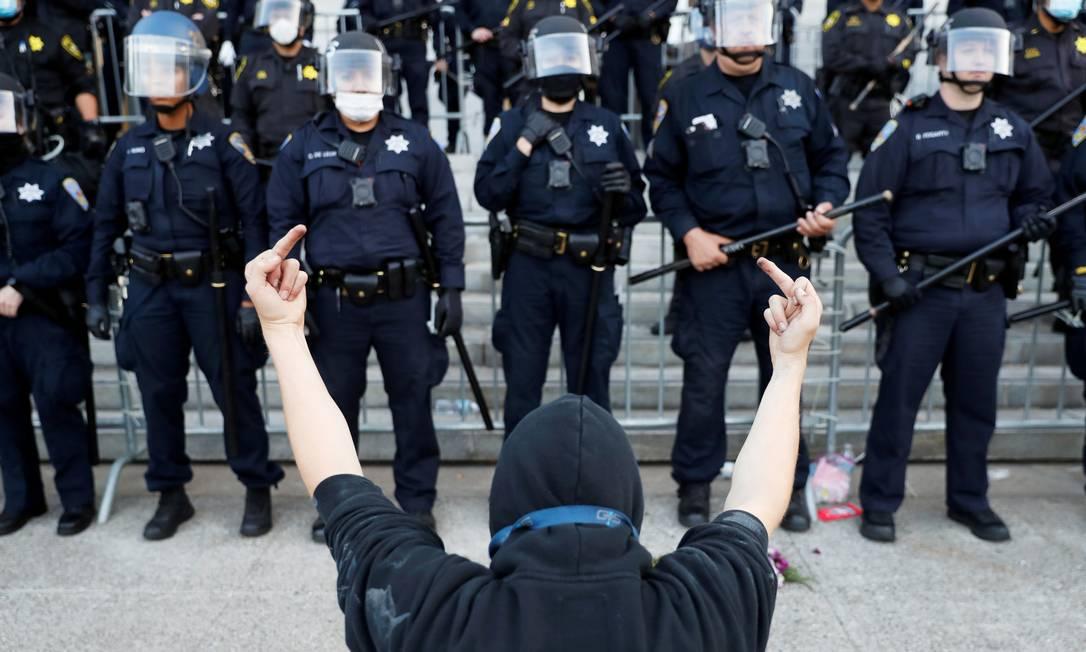 Manifestante insulta policiais com gesto durante protesto em São Francisco, Califórnia, no domingo Foto: STEPHEN LAM / REUTERS