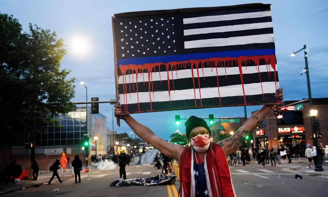 Manifestante exibe bandeira dos Estados Unidos retratada em preto e branco, com sangue escorrendo, durante protesto em Denver, Colorado, no domingo Foto: JASON CONNOLLY / AFP