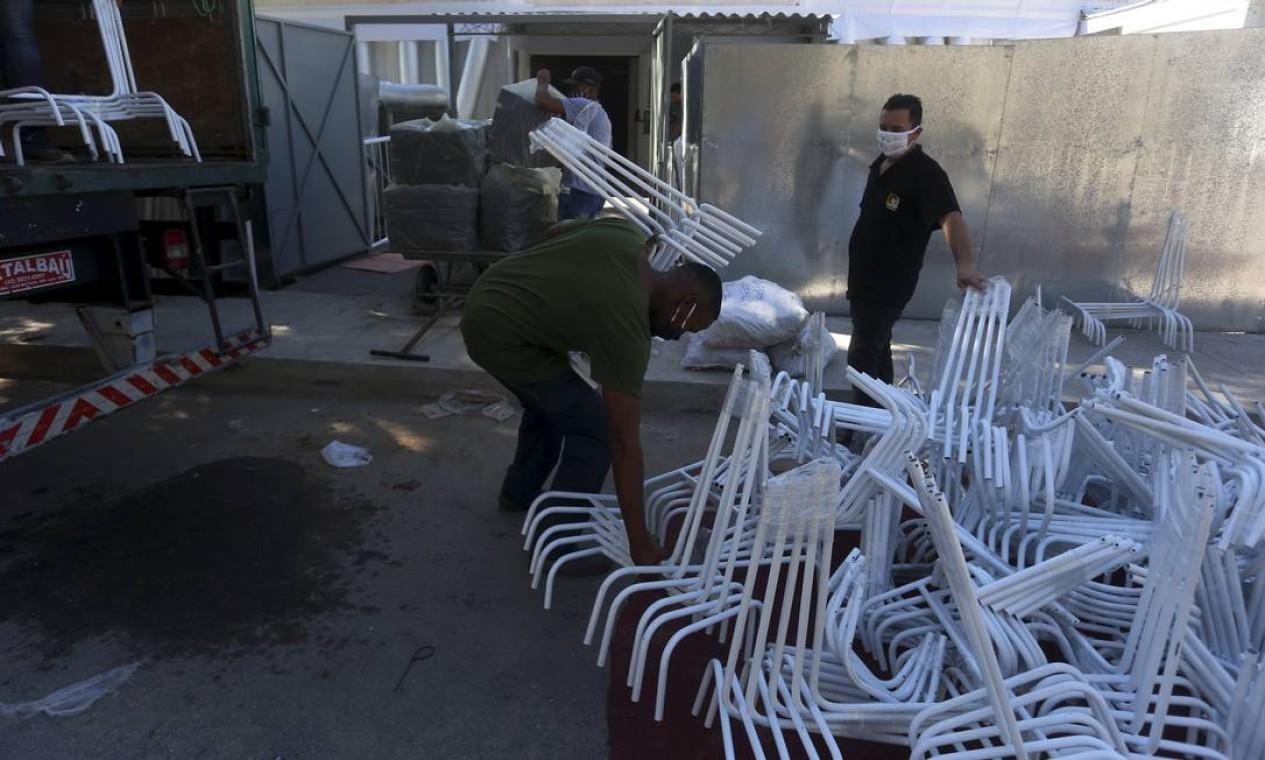 Operário descarregam ferragebs que serão usadas no hospital ded campanha de Caxias Foto: fabiano rocha / Agência O Globo