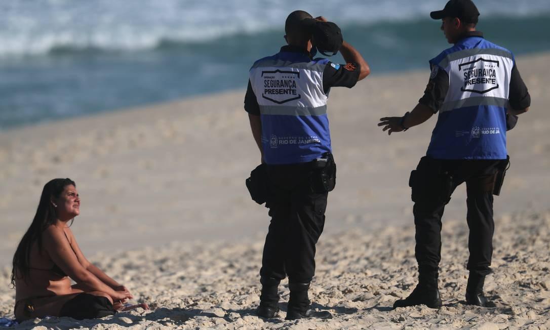 Policiais abordam banhista na areia da Praia do Recreio. Caminhadas no calçadão das praias e atividades esportivas individuais no mar, como natação ou surfe, estarão liberadas a partir desta terça-feira Foto: Luiza Moraes / Agência O Globo