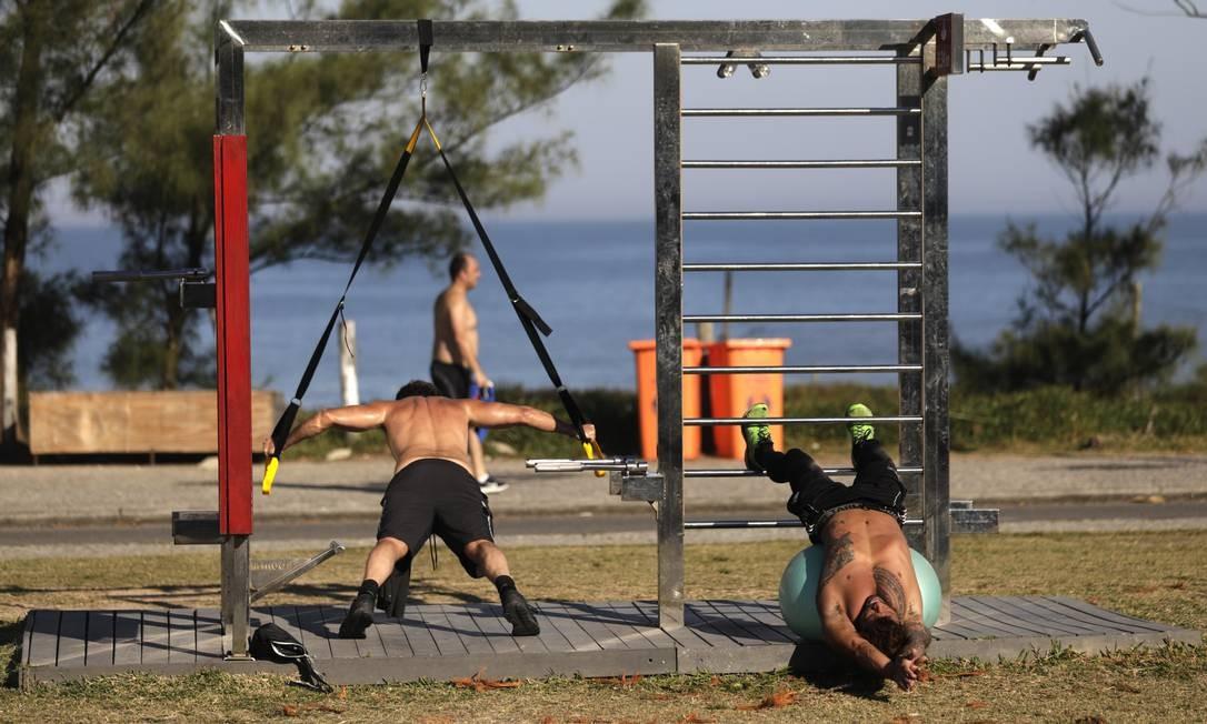 Dois homens fazem atividade física no orla da Praia do Recreio, o que só voltará a estar autorizado nesta terça Foto: Luiza Moraes / Agência O Globo