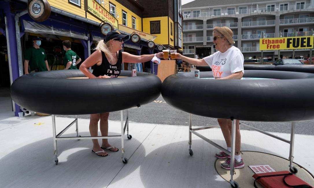 Clientes de um restaurante experimentam dispositivos de distanciamento social feitos de tubos de borracha em meio à pandemia de coronavírus, em Ocean City, Maryland, EUA Foto: ALEX EDELMAN / AFP