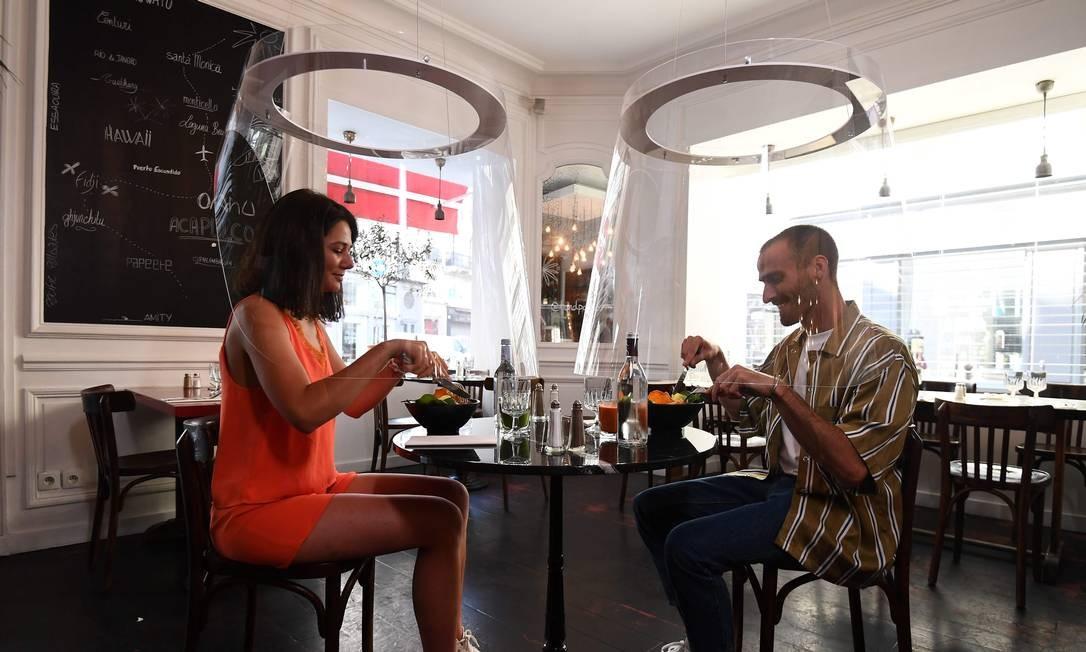 Casal almoça sob uma proteção no restaurante H.A.N.D, em Paris, enquanto a França facilita as medidas de bloqueio tomadas para conter a propagação da pandemia de COVID-19 Foto: ALAIN JOCARD / AFP