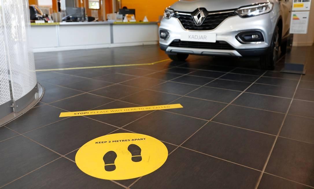 Adesivos sinalizam aos clientes sobre o distanciamento social de dois metros em uma concessionária de veículos reaberta nesta segunda-feira (1º), em Old Basing, perto de Basingstoke, sudoeste de Londres Foto: ADRIAN DENNIS / AFP