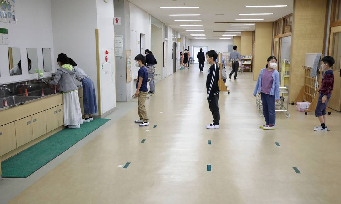 Crianças usando máscaras mantêm distância uma da outra em uma instalação de lavagem das mãos antes do almoço escolar em Tóquio, Japão Foto: STR / AFP