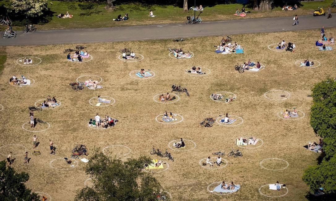 Na Holanda, pessoas aproveitam o sol dentro de círculos no parque no Euromast, em Roterdão Foto: SEM VAN DER WAL / AFP