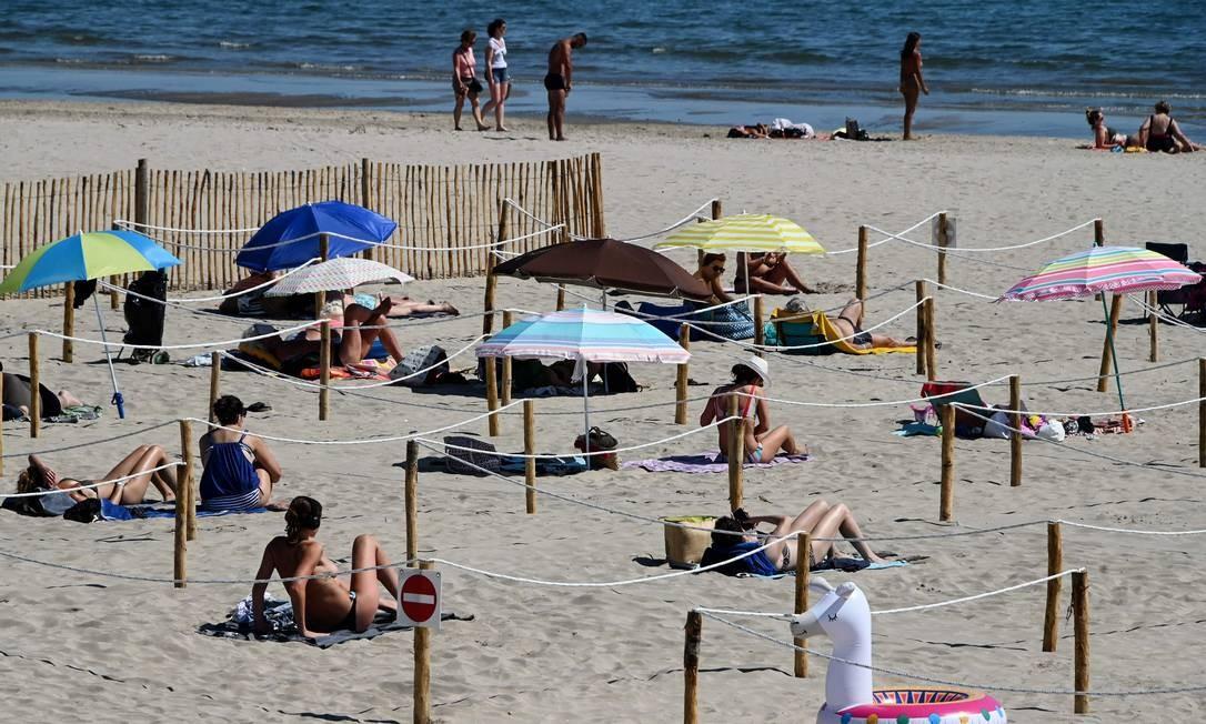 Pessoas tomam banho de sol em Sunset Beach, com áreas separadas para respeitar a distância social em La Grande-Motte, no sul da França Foto: PASCAL GUYOT / AFP