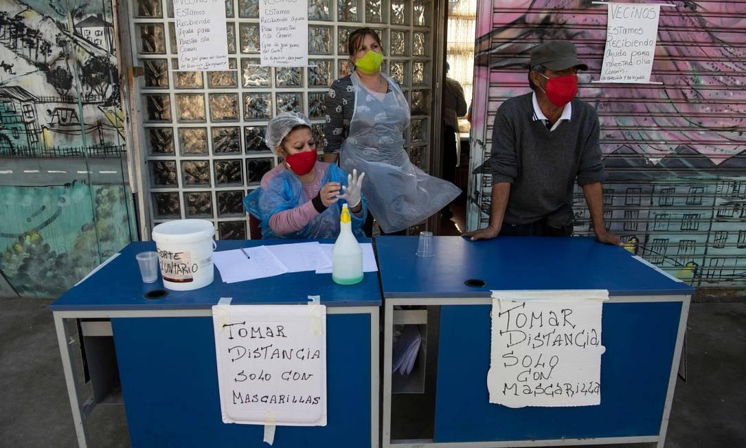 """Voluntários esperam, ao lado das placas em que se lê """"Manter distância. Somente com máscaras faciais"""", os residentes para um almoço solidário no bairro de La Pintana, Santiago, no Chile Foto: MARTIN BERNETTI / AFP"""