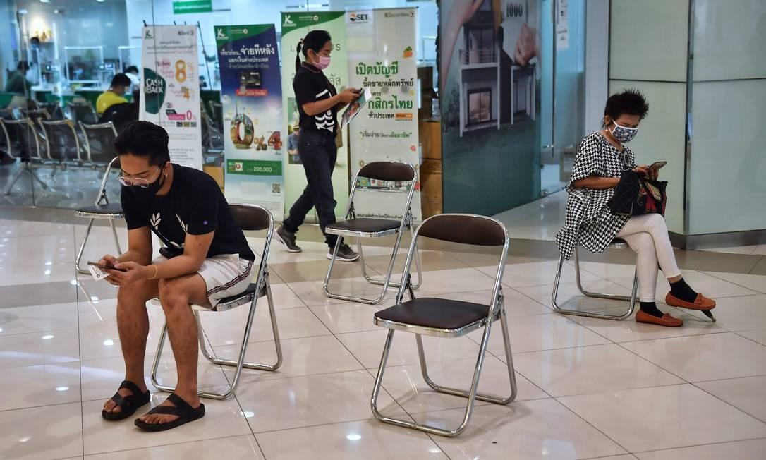 Pessoas esperam para entrar em um banco mantendo a distância social como medida preventiva contra o coronavírus, em um shopping em Bangkok Foto: LILLIAN SUWANRUMPHA / AFP