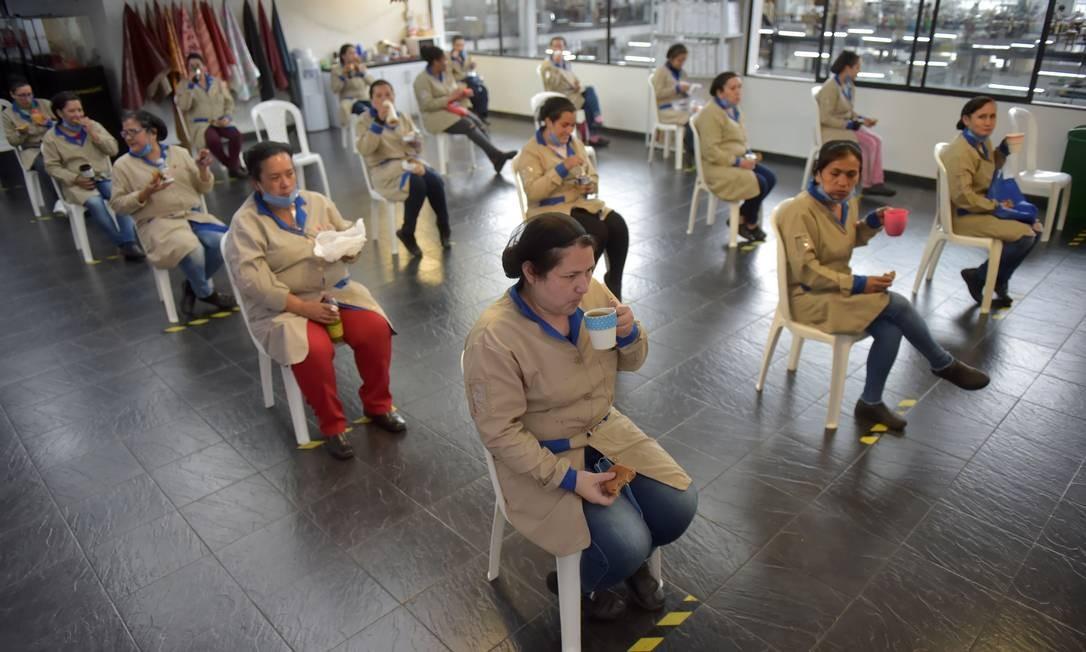 Funcionários fazem um lanche mantendo distância física, como medida preventiva contra a disseminação do novo coronavírus, em uma fábrica de artigos de couro em Bogotá Foto: RAUL ARBOLEDA / AFP