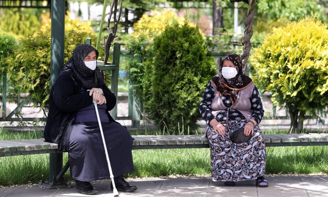 Idosos, usando máscaras protetoras, sentam-se em um banco de um parque do distrito de Akyurt, na Turquia Foto: ADEM ALTAN / AFP
