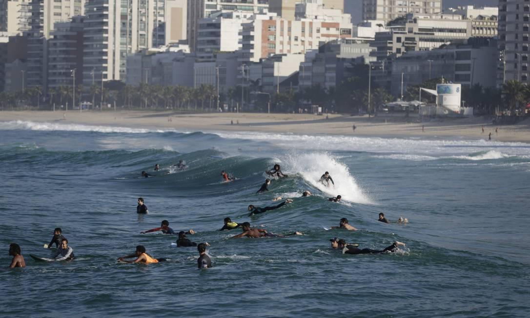 Arpoador ficou 'crowdeado', como dizem os surfistas, na manhã desta terça-feira. Esportes como natação e surf estão liberados. Já o banho de mar recreativo continua proibido Foto: Marcia Foletto / Agência O Globo