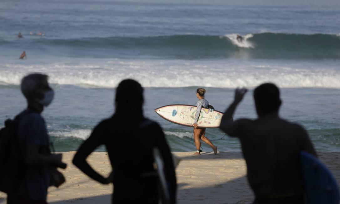 Homem, usando mascara de proteção, passa por surfistas à beira-mar Foto: Marcia Foletto / Agência O Globo