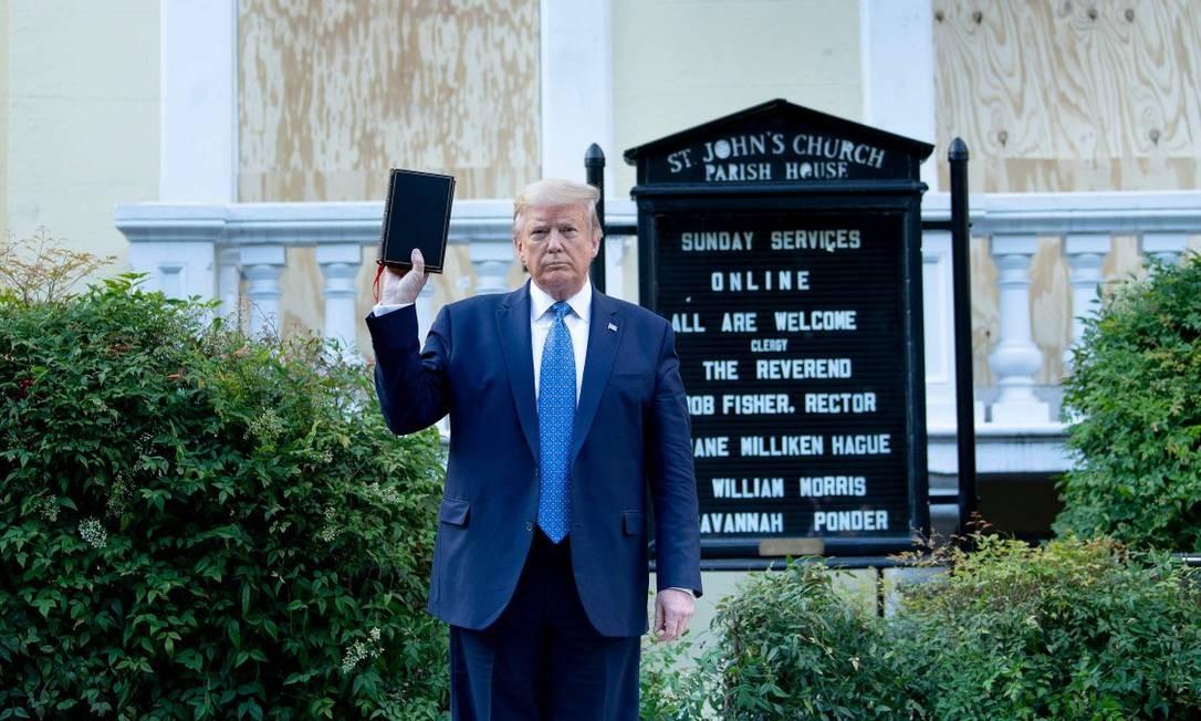 Erguendo uma Bíblia, Trump posa para fotos em frente à Igreja de São João, em Washington Foto: BRENDAN SMIALOWSKI / AFP