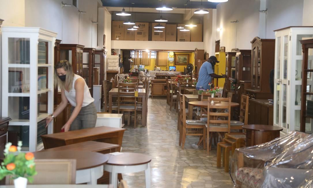 Funcionários fazem limpeza de uma loja de móveis na Tijuca, no primeiro dia da reabertura Foto: Pedro Teixeira / Agência O Globo