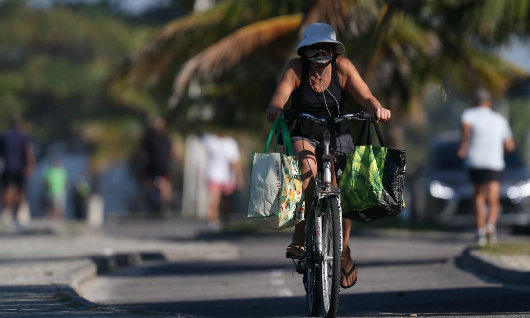 Uma mulher pedala pelo calçadão da Praia da Barra, Zona Oeste, no primeiro dia de reabertura da cidade em meio à pandemia de Covid-19 Foto: Luiza Moraes / Agência O Globo