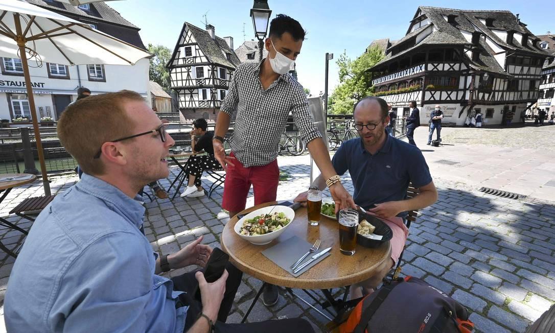 Um garçom usando máscara facial atende a clientes em um restaurante em Estrasburgo, no leste da França. Todos os cafés, bares e restaurantes do país estavam fechados desde 17 de março, quando o confinamento geral foi decretado pelo governo para conter o surto de COVID-19 Foto: FREDERICK FLORIN / AFP