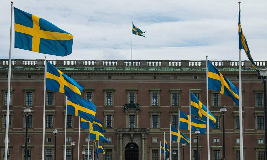 Bandeiras da Suécia em frente ao Palácio Real de Estocolmo Foto: JONATHAN NACKSTRAND / AFP / 29-5-2020