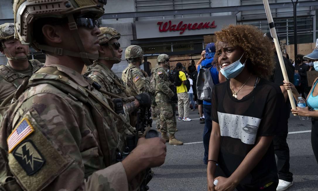 Manifestante conversa com membro da Guarda Nacional dos Estados Unidos, que porta um fuzil diante de protesto, em Los Angeles (a cena continua na próxima foto) Foto: BRENT STIRTON / AFP