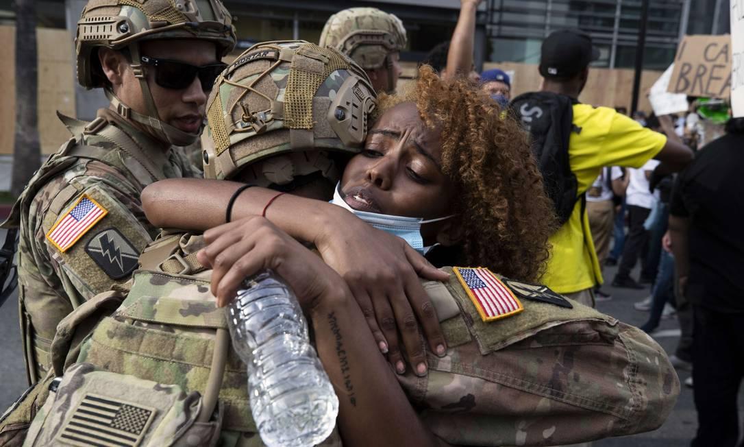 Um abraço negro. A cor da pele falou mais alto do que a farda da tropa que foi incentivada a disparar contra manifestantes em tweet do presidente Donald Trump, que foi advertido pelo Twitter Foto: BRENT STIRTON / AFP