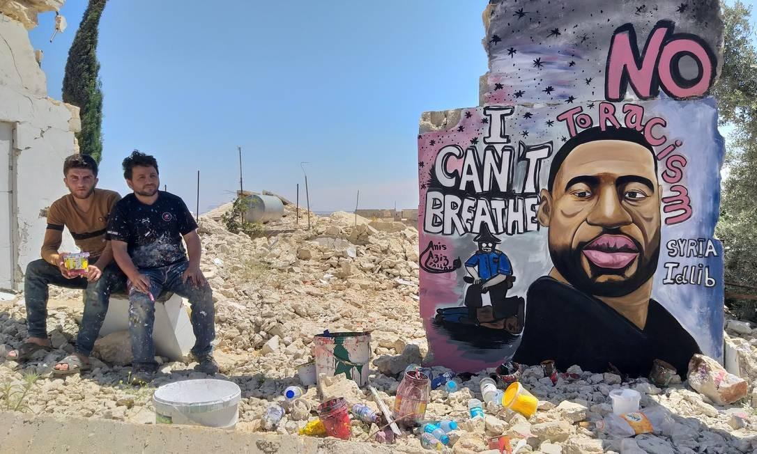 Artistas Aziz Asmr e Anis Hamdoun posam próximo a grafite com a imagem de George Floyd, em Idlib, na Síria, na segunda-feira, quando o assassinato completou uma semana Foto: MOHAMAD JAMALO / MOHAMAD JAMALO via REUTERS