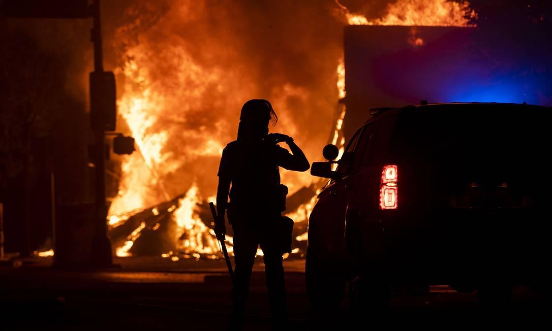 Policial em frente a uma loja que foi queimada por manifestantes em Minneapolis Foto: Stephen Maturen / AFP