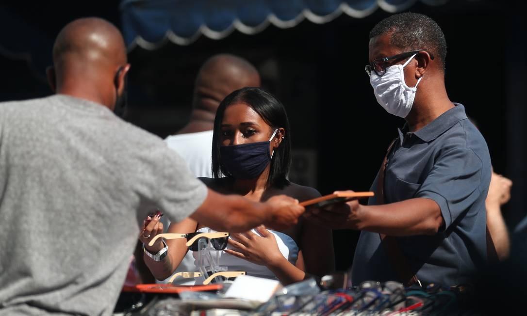 Cliente experimenta óculos em barraca de camelô da Uruguaiana, no centro do Rio Foto: Luiza Moraes / Agência O Globo