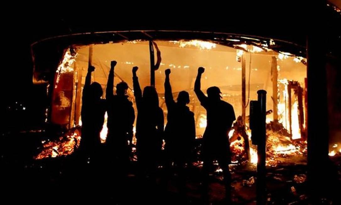 Manifestantes posam do lado de fora de loja de bebidas em chamas nos Estados Unidos Foto: REUTERS