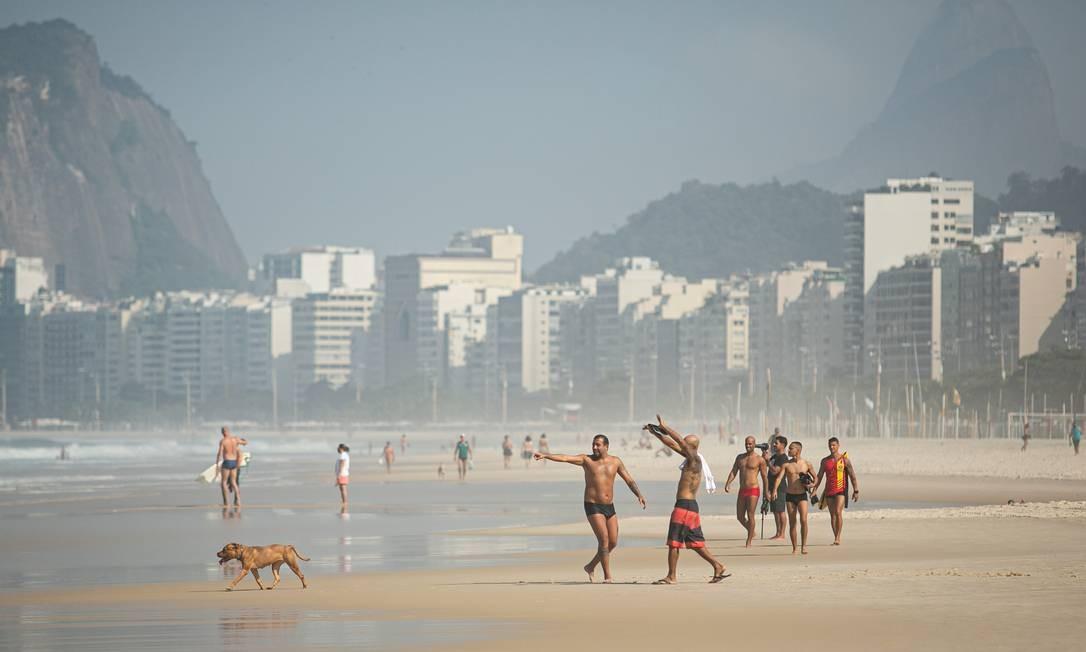 Na falta de policiamento na Praia do Leme, banhistas aprovitavam a manhã para tomar banho de mar, o que ainda nçao está liberado. Apenas práticas esportivas, como surfe e natação, estão permitidas na água Foto: Hermes de Paula / Agência O Globo