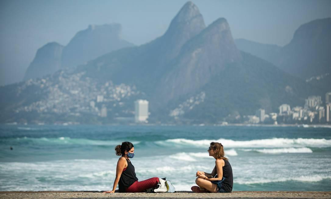 Na orla de Ipanema, duas mulheres conversam sentadas no calçadão, uma delas sem máscara. Uso do acessório de proteção continua sendo obrigatório Foto: Hermes de Paula / Agência O Globo