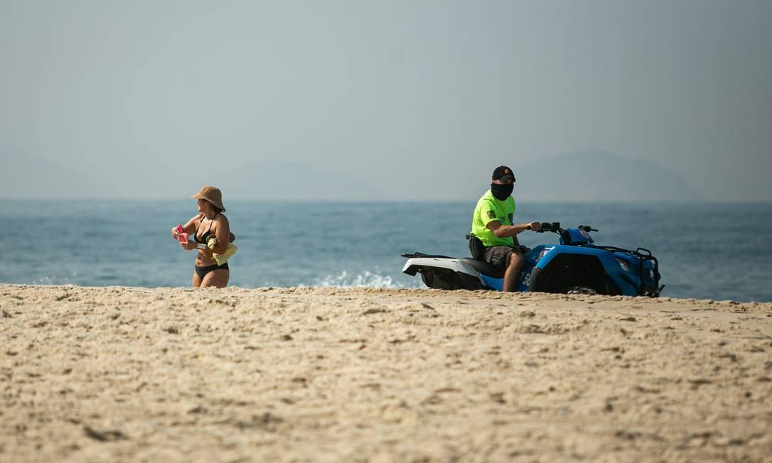 Um policial orienta banhista a deixar a areia da Praia de Copacabana Foto: Hermes de Paula / Agência O Globo