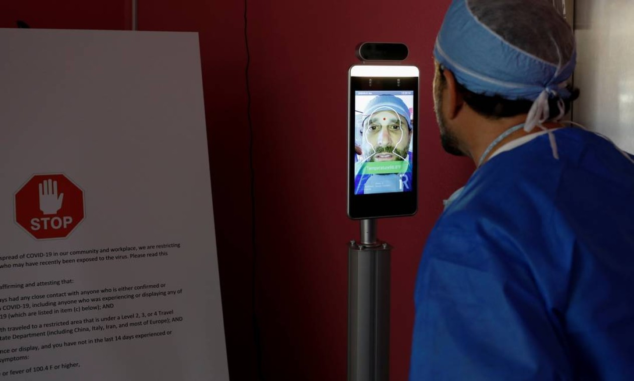 Michael Salzhauer usa dispositivo para medir a temperatura do corpo enquanto conduz injeções de Botox na garagem de sua clínica Foto: MARCO BELLO / REUTERS
