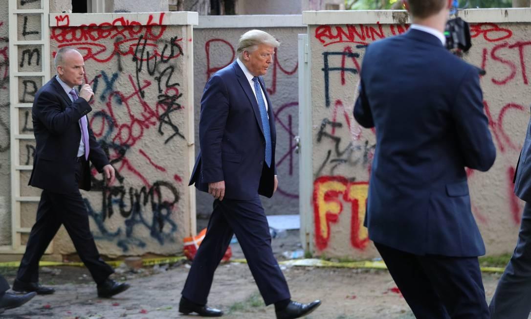 Donald Trump passa diante de prédio coberto por pichações perto da Casa Branca, no dia 1º de junho Foto: TOM BRENNER / REUTERS