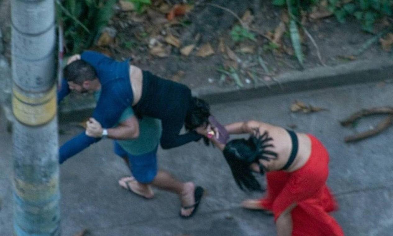 Mulher de calça vermelha e blusa preta puxa os cabelos de Ticyana Foto: Reprodução