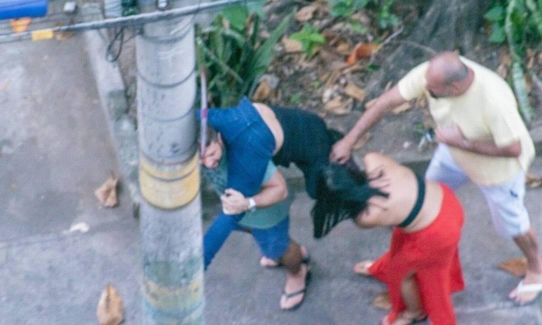 Enquanto mulher de calça vermelha puxa os cabelos da médica, homem de blusa amarela dá socos em Ticyana Foto: Reprodução