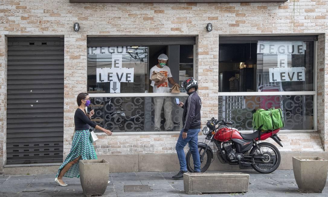 Contato mínimo no 'novo normal': no Spoleto, em Niterói, funcionário entrega pedido a motoboy. Serviço de delivery foi a forma encontrada pelos comerciantes para driblar fechamento de estabelecimentos devido à pandemia Foto: Ana Branco em 28-5-2020 / Agência O Globo